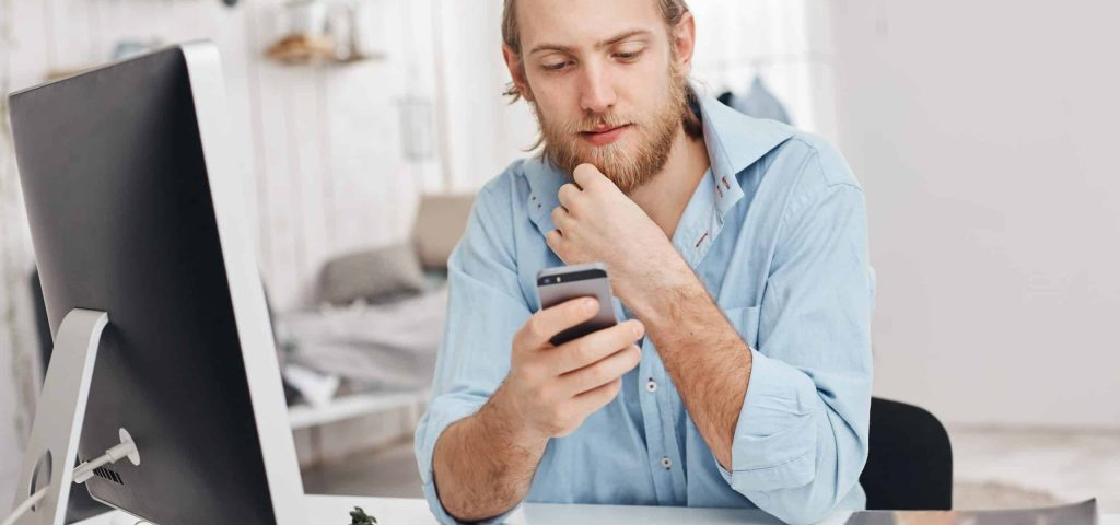 Portrait of handsome fair-haired bearded male freelancer installs new application on smart phone, downloads program on computer, uses wireless internet connection, recieves email or message from partner. Business, modern technologies and communication